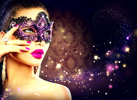 Sexy woman wearing carnival mask over holiday dark background Foto de archivo