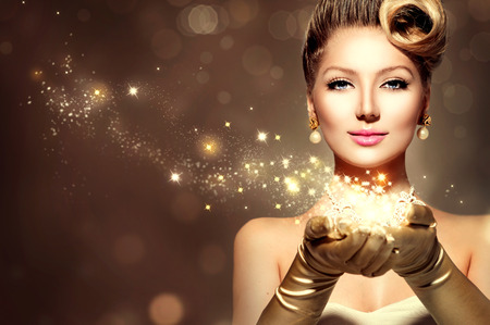 golden light: Holiday retro woman with magic stars in her hands. Christmas Stock Photo