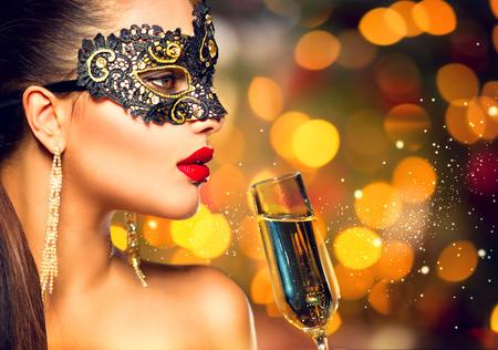 Modello sexy donna che indossa maschera di carnevale con un bicchiere di champagne