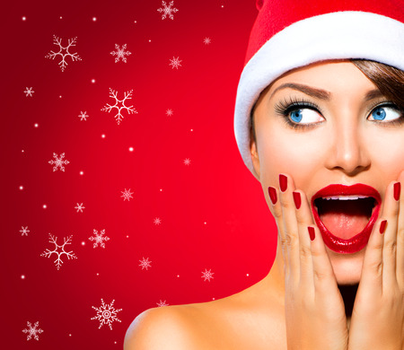 holiday backgrounds: Christmas Woman. Beauty Model Girl in Santa Hat over Red Stock Photo