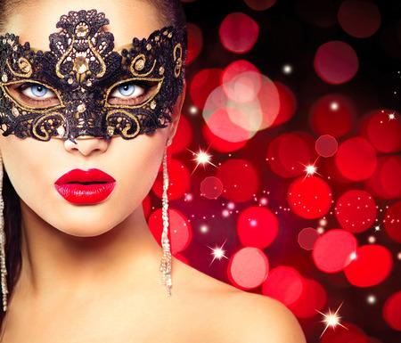 aretes: La mujer llevaba máscara de carnaval sobre fondo rojo brillante Foto de archivo