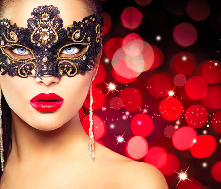 black mask: Woman wearing carnival mask over glowing red background