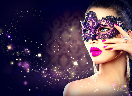 masquerade: Sexy woman wearing carnival mask over holiday dark background Stock Photo