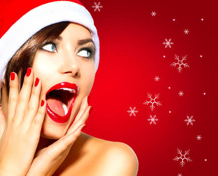 hand in mouth: Christmas Surprised Winter Woman. Beauty Model Girl in Santa Hat