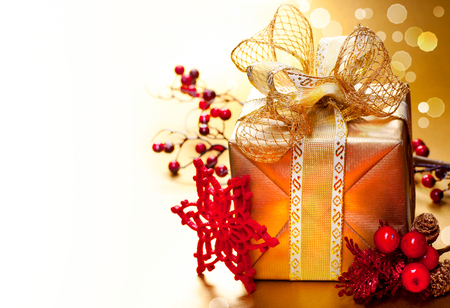 holiday tradition: Decorated Christmas golden gift box with baubles