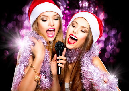 Christmas party, karaoke. Beauty girls in santa hats singing Stock fotó