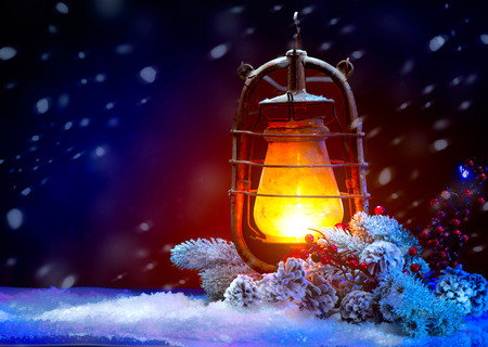 old styled: Christmas Holiday Scene. Burning Old Styled lantern in the evening Stock Photo