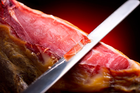 iberian: Jamon serrano. Traditional spanish ham. Slicing hamon iberico