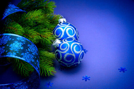 blue backgrounds: Christmas blue baubles with ribbon over blue background Stock Photo