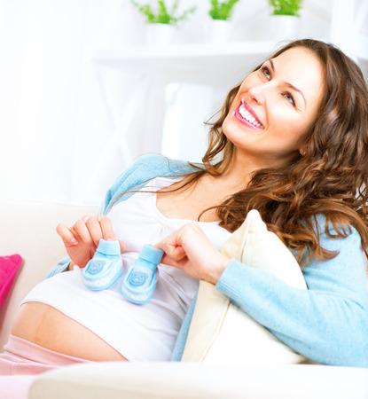 rodzina: Ciężarne szczęśliwa kobieta niebieskie buciki w dłoniach Zdjęcie Seryjne