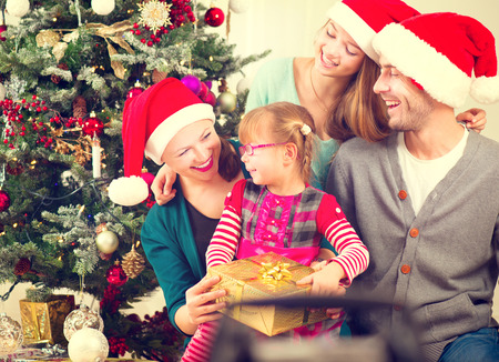 kid smiling: Christmas family with kids opening christmas gifts