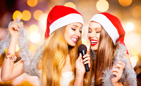 Christmas party, karaoke. Beauty girls in santa hats singing Stock Photo