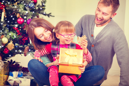 Christmas family with little daughter opening Christmas gifts photo
