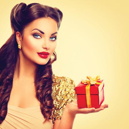 femme brune: Beaut� Pin Up Girl avec bo�te-cadeau de vacances dans sa main