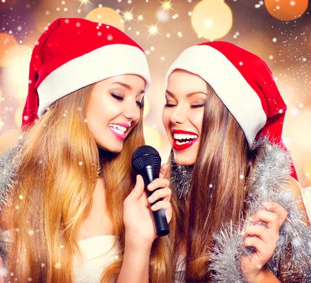 Christmas party, karaoke. Beauty girls in santa hats singing photo