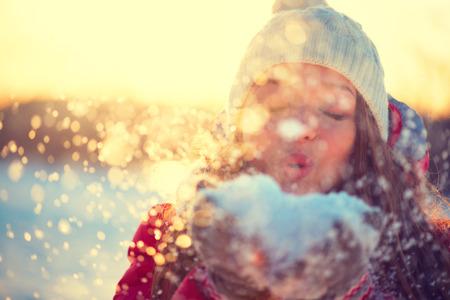 Schoonheid winter meisje waait sneeuw in ijzige park. Zonnige dag