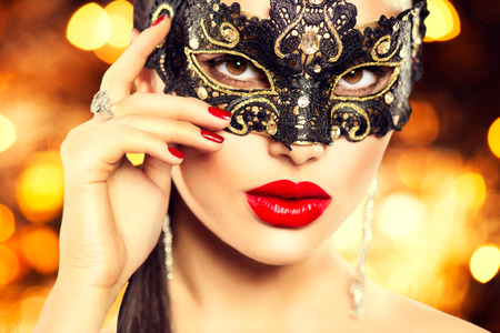Sexy woman wearing carnival mask over holiday glowing background photo