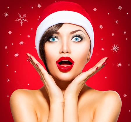 クリスマス驚きの冬の女性。サンタの帽子の美少女モデル