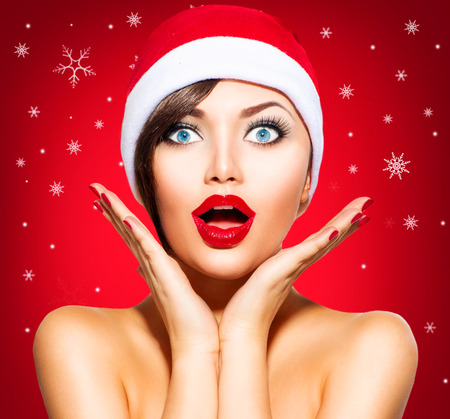 make a gift: Christmas Surprised Winter Woman. Beauty Model Girl in Santa Hat