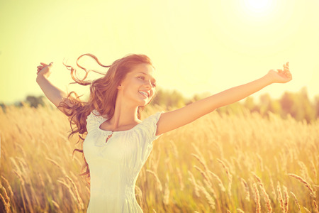 Beauty happy girl with blowing hair enjoying nature on the field Standard-Bild