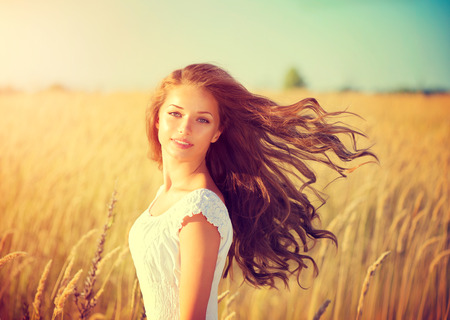 wild hair: Beautiful teenage model girl in white dress enjoying nature