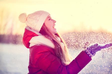 Muchacha de la belleza del invierno sopla nieve en parque escarchado. Día soleado