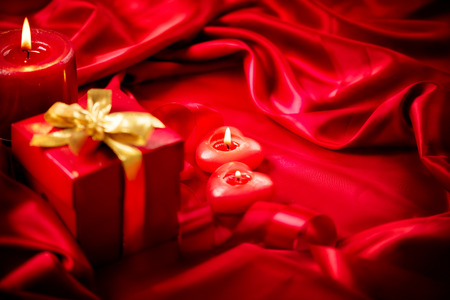 Valentine red heart shaped candles and gift on red silk photo