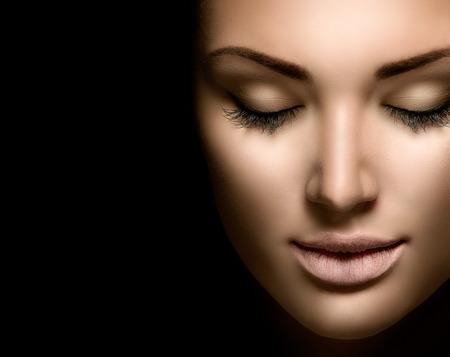belle brunette: femme de beaut� visage gros plan isol� sur fond noir Banque d'images