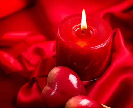 Valentines Day. Valentine red hearts and candle on red silk photo