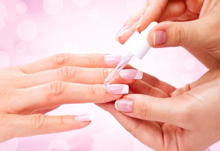Manicura, aceite de manos spa cutícula. Hermosa mujer da el primer