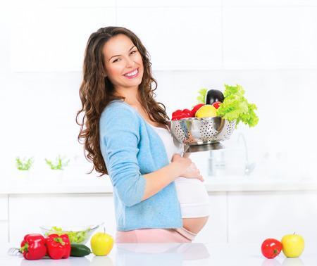 embarazada: Embarazadas jóvenes verduras mujer cocina. La comida sana