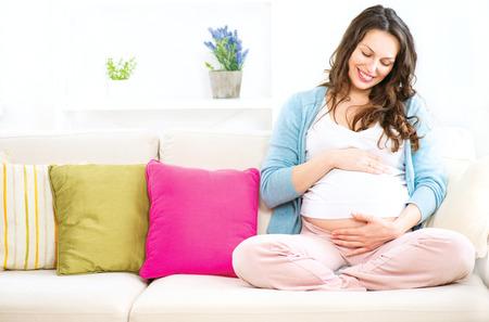 âhealthy: Mujer embarazada sentada en un sofá y acaricia su vientre Foto de archivo