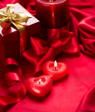 Valentines Day. Red heart shaped candles and gift on red silk photo