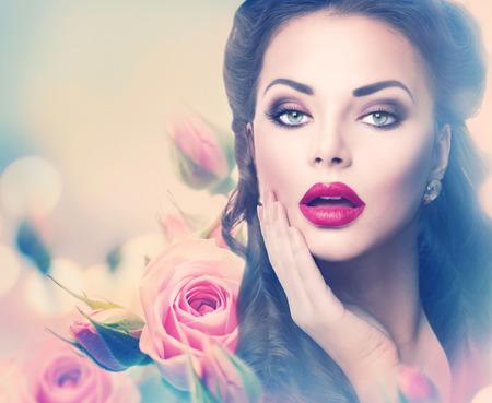 Retro vrouw portret in roze rozen. Vintage stijl portret Stockfoto