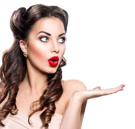 cara sorprendida: Mujer sorprendida que muestra el espacio vacío de la copia en la mano abierta