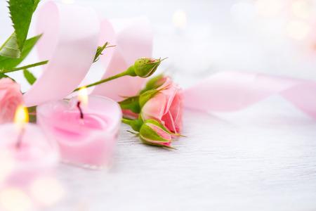 Valentijnsdag. Roze hart vormige kaarsen en rose bloemen Stockfoto