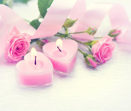 バレンタインの日。ピンクのハート形の蝋燭およびばら色の花