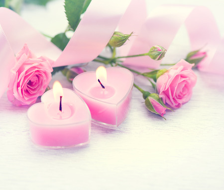 Valentines Day. Pink heart shaped candles and rose flowers Stockfoto