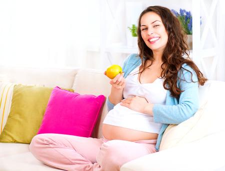 embarazada feliz: Mujer embarazada feliz que se sienta en un sofá y que come la manzana