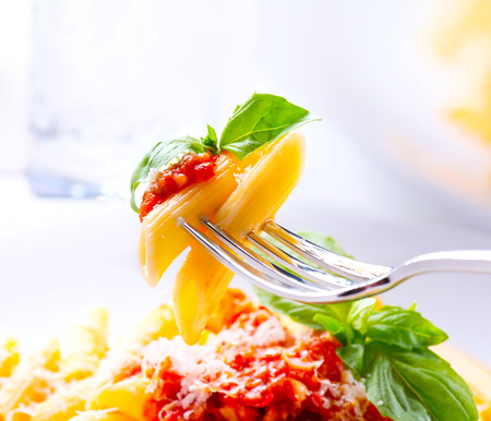 sana?a: Pasta. Penne pasta con salsa boloñesa en un Tenedor Foto de archivo