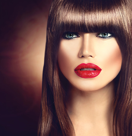 coloring lips: Beautiful brunette woman with fashion fringe haircut