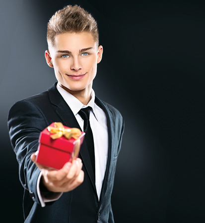 gray eyes: Young handsome man giving red gift box. Elegant businessman