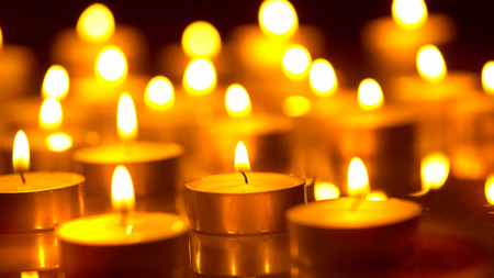 by light: Candles light background. Holiday candles closeup Stock Photo