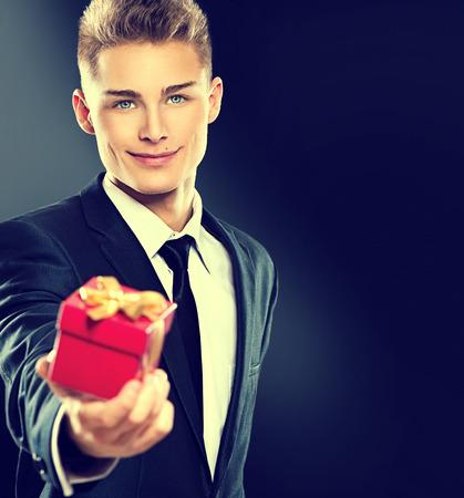 gift tie: Hombre joven hermoso que da el rect�ngulo de regalo rojo Foto de archivo