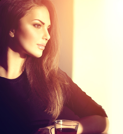brown cup tea: Beautiful brunette girl drinking tea or coffee in cafe