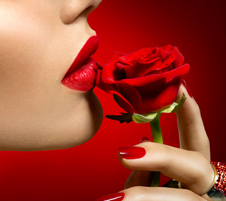 Beautiful model woman kissing red rose flower. Sexy red lips