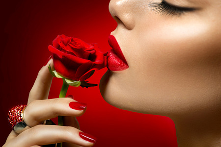 red nail colour: Beautiful model woman kissing red rose flower Stock Photo