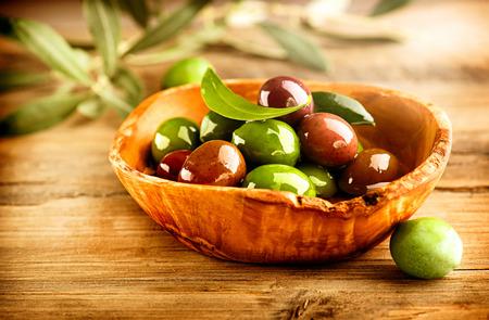 Olive e olio d'oliva sul tavolo di legno