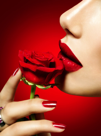 lip kiss: Beautiful model woman kissing red rose flower. Sexy red lips