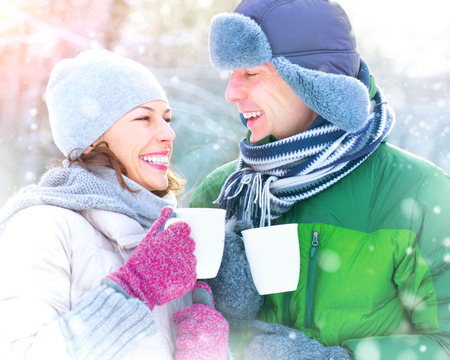 winter couple: Happy winter couple drinking hot beverage outdoors